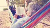 glückliche Seniorin liest Buch im Herbst am See - 176846384