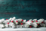 Christmas tree branch with red berries over aged wooden background - 176849767