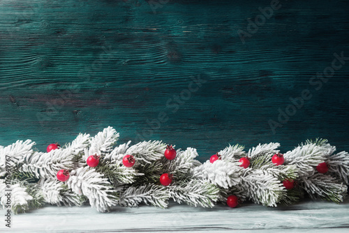 Christmas tree branch with red berries over aged wooden background