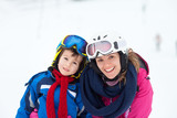 Sweet young boy and his mother, learning to ski on a mild ski slope in Austrian ski resort - 176849935