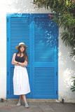 A girl is posing by the blue door - 176854119