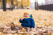 happy little boy in the sun in autumn, sitting in leaves and yellow cute hat