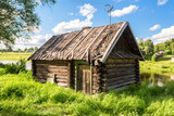 Traditional russian old wooden bath at the bank of river in sunny summer day - 176858150