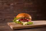 Burger on a wooden board on wooden table over dark background - 176858303
