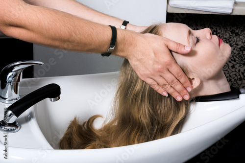 A young woman is preparing to wash her head in a beauty salon.