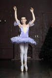 Young ballerina dancing gracefully against black background. - 176858737