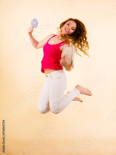 Positive woman jumping holds lollipop candy in hand Poster