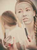 Woman with grey clay mud mask on her face - 176864575