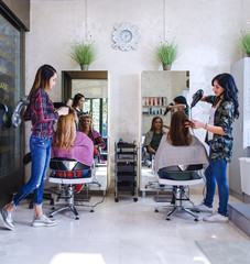 Working day inside the hair salon, hairdressers making hairstyle on two young woman. © PointImages
