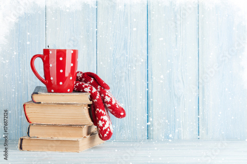 Fotobehang Chocolade Hot chocolate cup and mittens over books