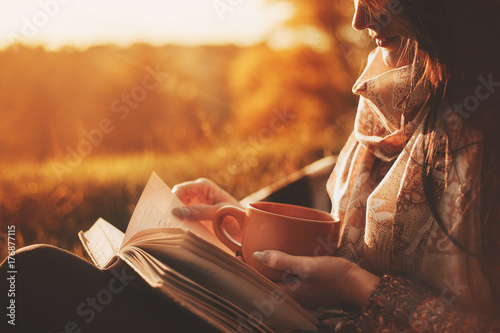 fototapeta na ścianę a woman sits near a tree in an autumn park and holds a book and a cup with a hot drink in her hands. Girl reading a book