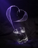 glass with water in the form of heart on a black background - 176893339