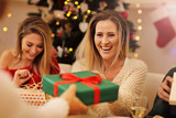 Group of friends giving Christmas presents at home - 176895973