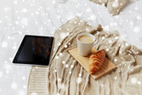 tablet pc, coffee and croissant on bed at home - 176901380