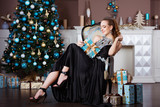 Holidays, celebration and people concept - young woman in elegant dress over christmas interior background - 176903740