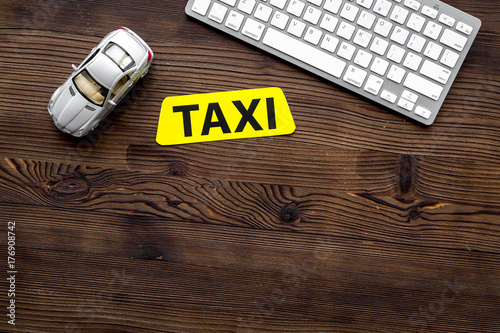 Plakat app for order a taxi online with car toy and keyboard on wooden background top v