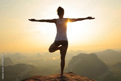 Plakat young fitness woman meditating on sunrise mountain peak