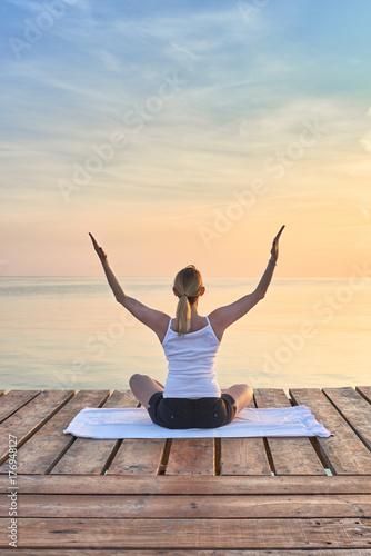 Plakat Schlanke Frau macht Yoga am Meer