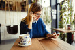 Beautiful young woman using digital tablet at coffee shop