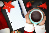 Woman in Santa's clothes holding a cup of hot tea on Christmas background, near an empty wish list - 176957177