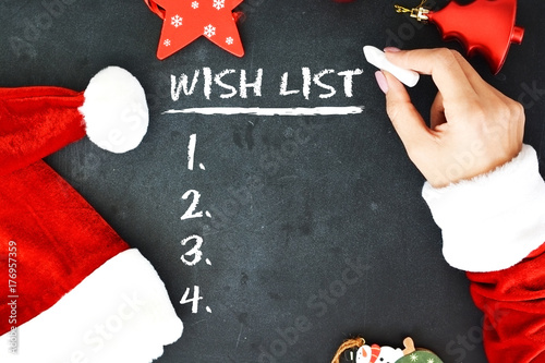 Mrs. Santa's hands writing a wish list on chalkboard - 176957359