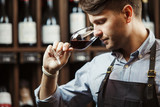Bokal of red wine on background, male sommelier appreciating drink - 176965976
