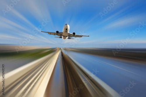 Airliner over highway on blurred background