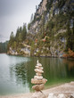 Quadro Stack of stones placed on shore of lake in mountains.