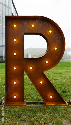 Foto Murales Rusty metal letter R with led light bulbs.
