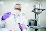 Close up of a scientist with face mask and gloves working with red liquid in a tube. - 176976733