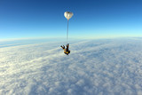 Skydiving. Tandem above white clouds.