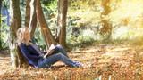 Frau sitzt entspannt im wald und liest ein buch. - 176980370