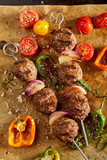 Roasted meatballs with vegetables lying on paper - 176982941