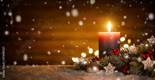 Kerze mit festlicher Dekoration und Holz Hintergrund bei fallendem Schnee, ideal für Advent und Weihnachten - 176985121