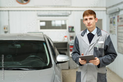Portrait of a car mechanic in a car workshop, in the background of service.