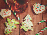 Cup mug of tea, gingerbread in the form of a Christmas tree and candy canes on a wooden background. Toned photo. - 176994196