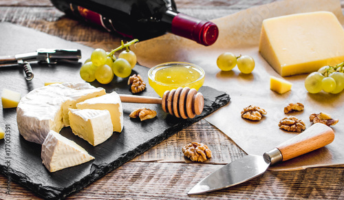 bottle of red wine, appetizers and corkscrew on wooden backgroun