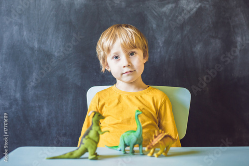 Boy showing a dinosaur as a paleontologist Poster