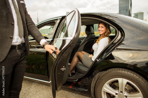 Handsome man holding car door for beautiful businesswoman Poster