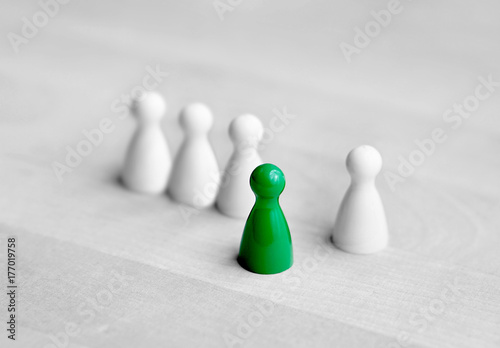 Volunteering, courage and being initiative or spontaneous concept. Dare to be different. One board game pawn stand in front from the crowd.