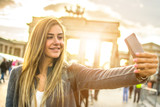 Pretty blonde woman taking a selfie in front of the Brandenburg Gate in Berlin, Germany.