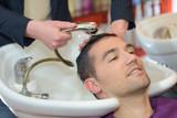 barber washing head client in barbershop - 177031383