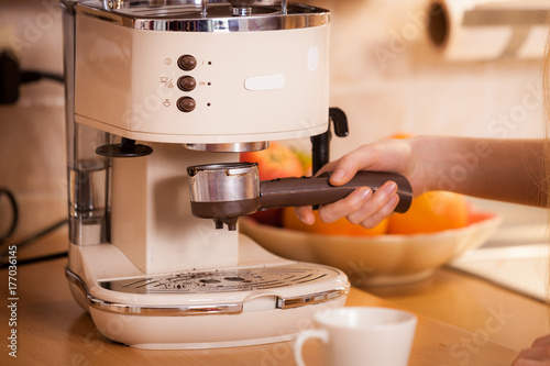 Papiers peints Cafe Woman in kitchen making coffee from machine