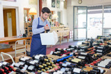 smiling seller man wearing apron promoting wine in wine store - 177037137