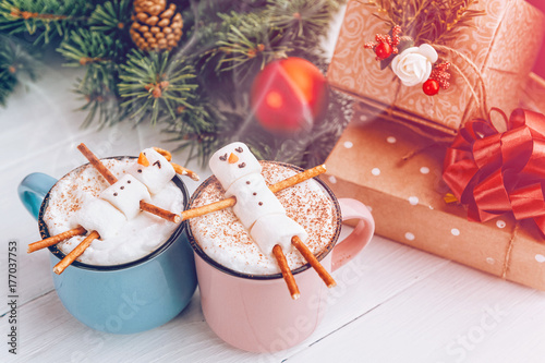 Foto op Canvas Chocolade a mug with hot chocolate on a wooden table with a marshmallow man who is resting in a mug