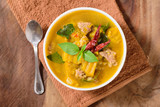 Thai food.Spicy pumpkin soup with pork in a bowl on brown fabric and wooden background.Top view of food - 177069376