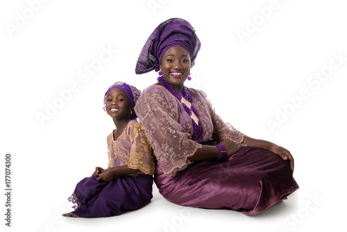 Plakát Beautiful African woman and lovely little girl sitting on floor in traditional p