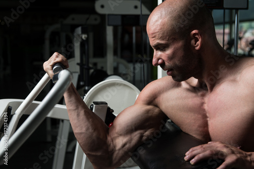 Biceps Exercise In A Gym On Machine Poster