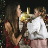Cute baby and mum decorating a Christmas tree. Red balls. - 177078944