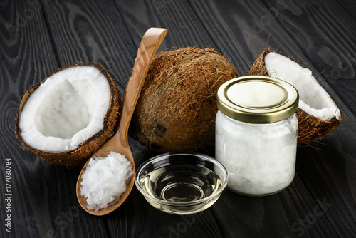 Coconut, glass jar and wooden spoon with coconut oil on a wooden background.
